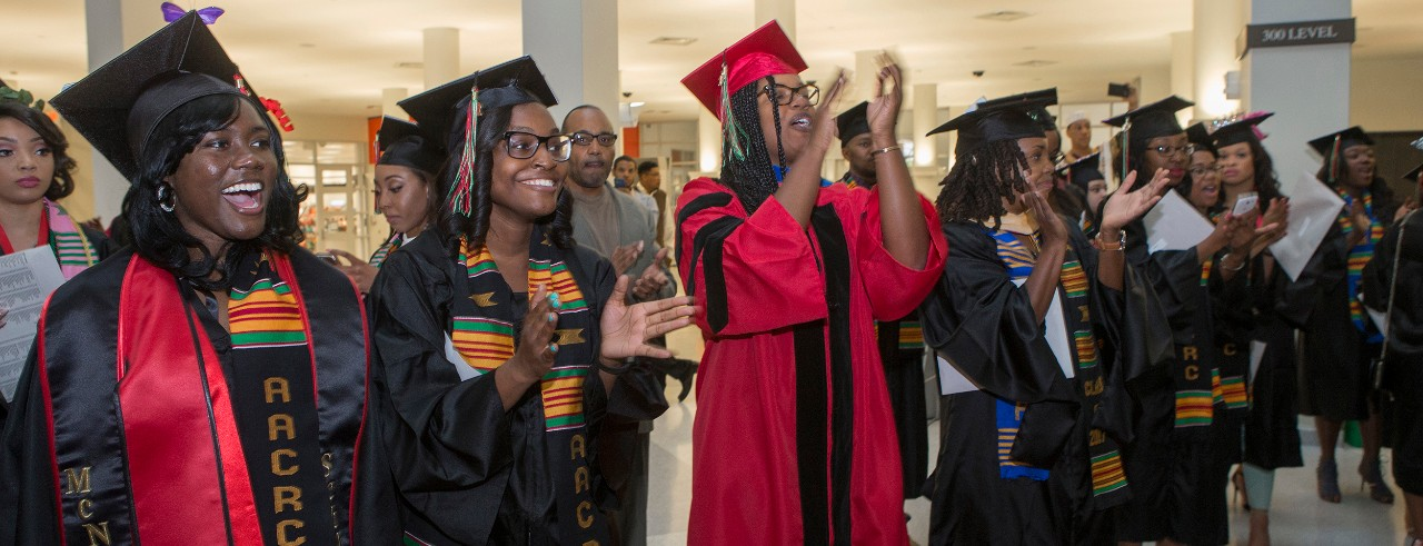 UC students and faculty celebrate Tyehimba in commencement regalia.