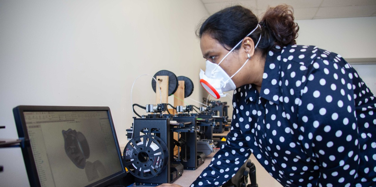 A UC student wearing a custom face mask looks at a laptop image of the design.
