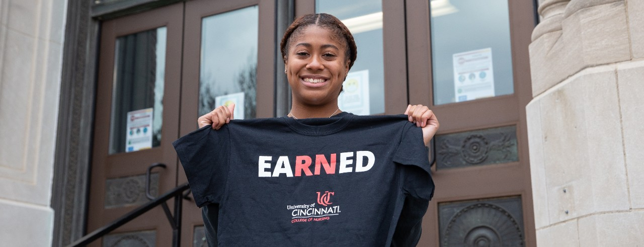 Alex Lewis holds up her new UC gear from the UC College of Nursing
