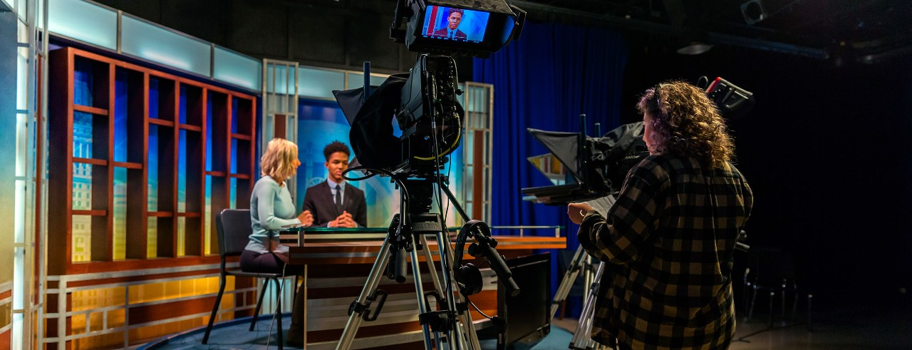 Students working in a news room studio