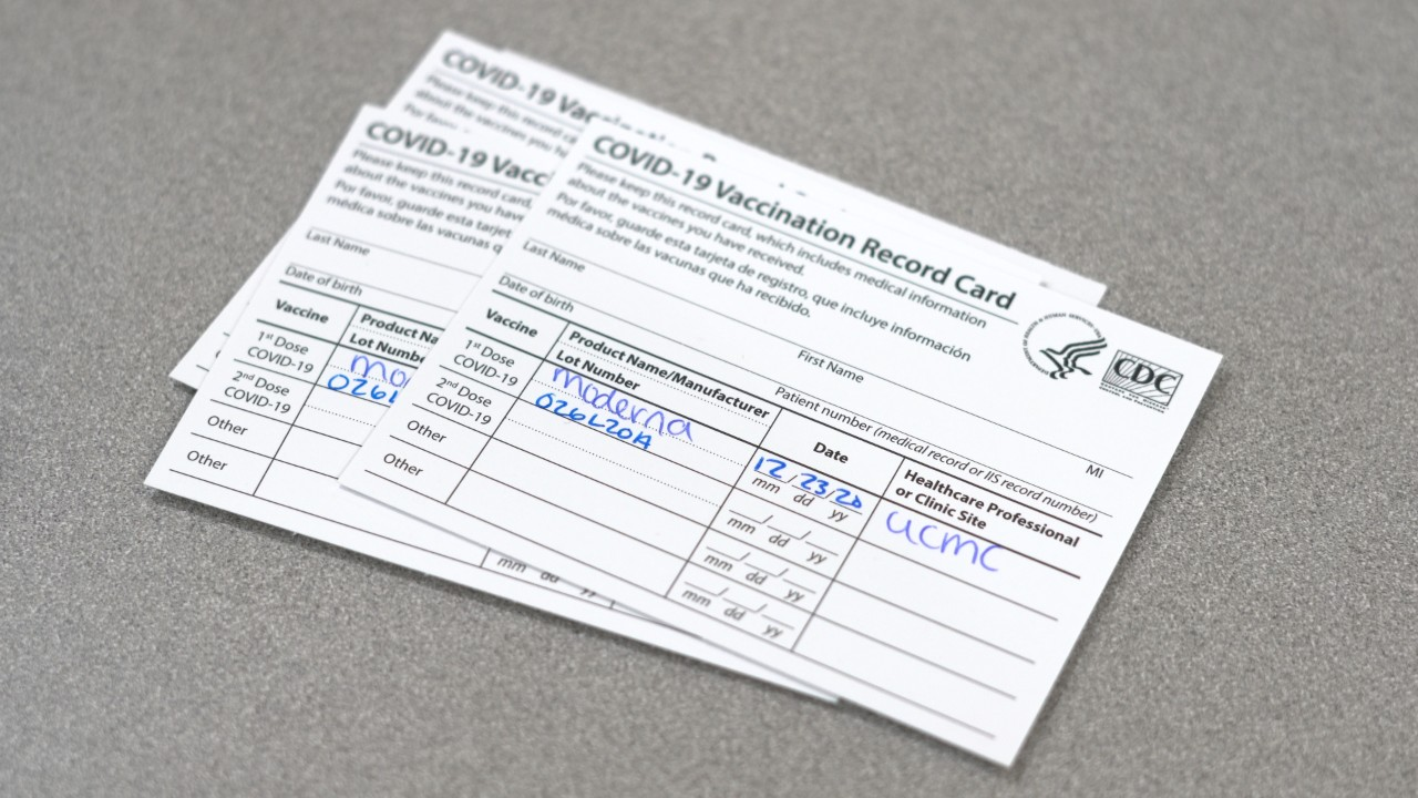 three cards showing the holder received the COVID-19 vaccine
