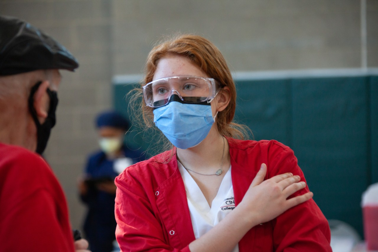 a nursing students consults with a patient at a COVID-19 vaccine clinic
