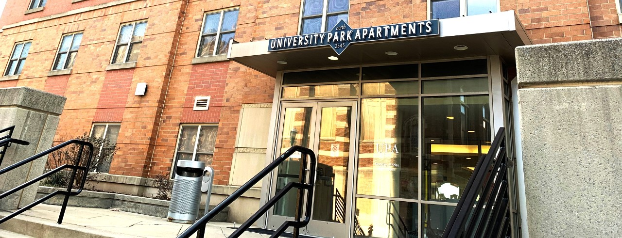 "Doorway to an orange brick building with concrete paver stairs, black railings and glass doors topped with an overhang with a sign that says ""University Park Apartments"""
