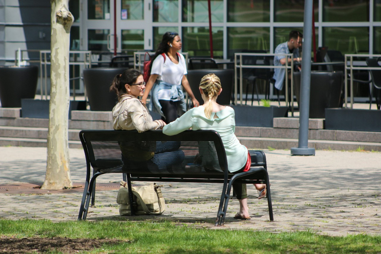 Two women sit on a bench and chat