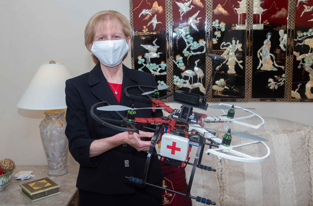 Debi Sampsel, director of telehealth in UC's College of Nursing, holds a telehealth drone that can respond to a patient's home. It has a video screen and a cargo container for medicine. Photo/Joseph Fuqua II/UC Creative + Brand