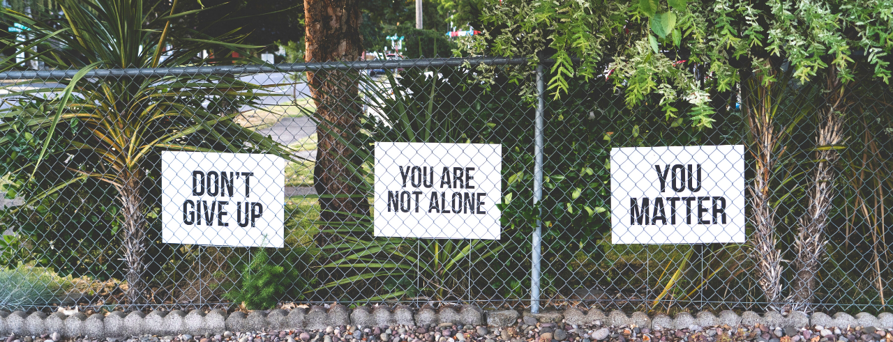 """a chainlink fenceline with signs that read, """"don't give up; you are not alone; you matter"""", s trees and bushes behind"""