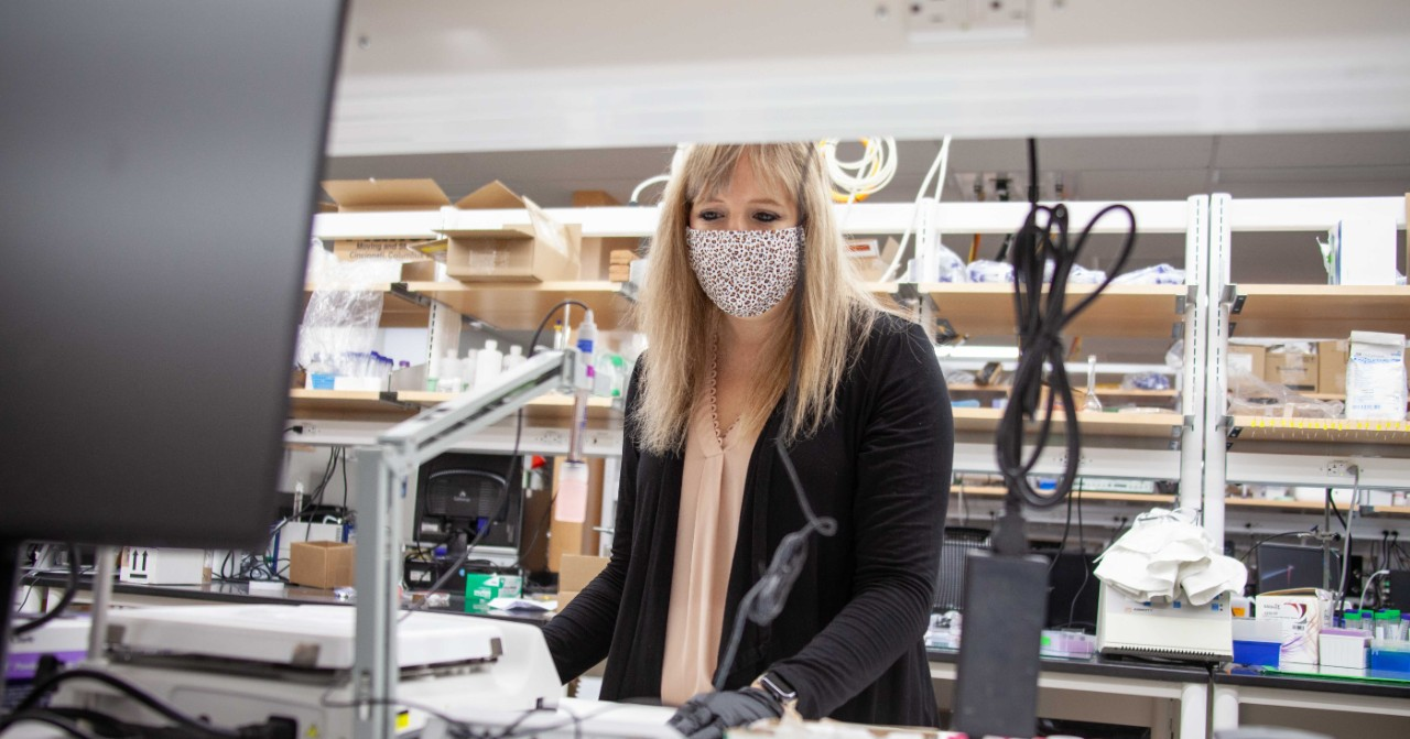 Ashley Ross wearing a face mask and gloves poses for a photo in her lab.