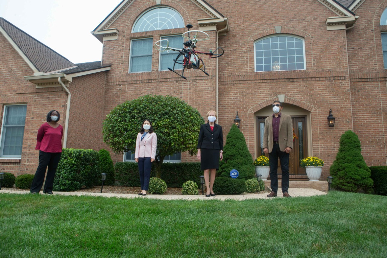 Four people socially distanced and in face masks stand outside a home with a drone hovering over them.