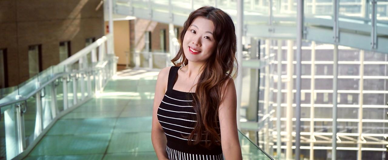 UC pharmacy PhD grad Tianyi Liu stands on UC's College of Medicine atrium bridge.