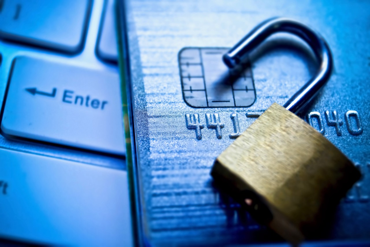 An open lock and credit card on top of a laptop keyboard