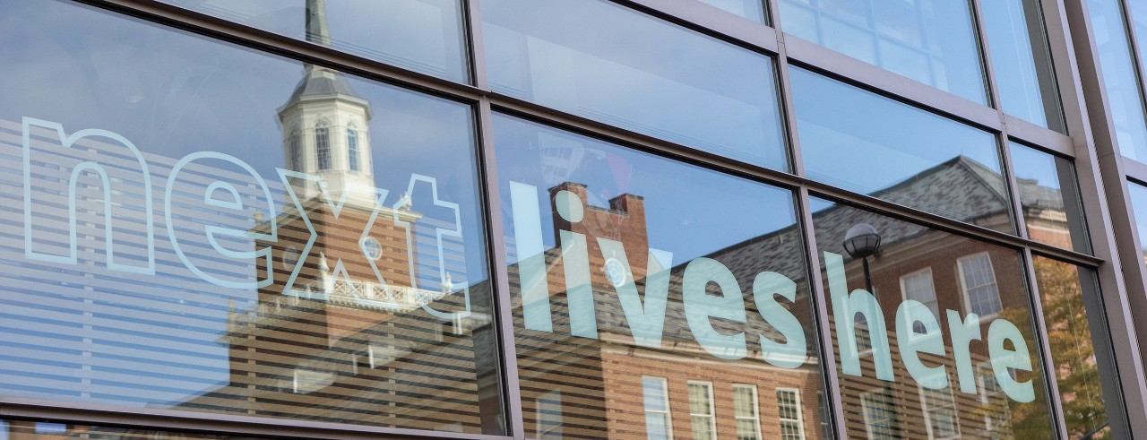"""McMicken hall reflected in windows with """"Next Lives Here"""" sign on them"""