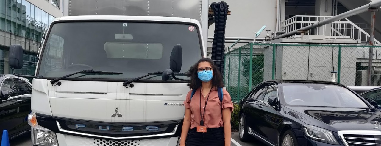 Young woman stands in front on an electric truck in Japan