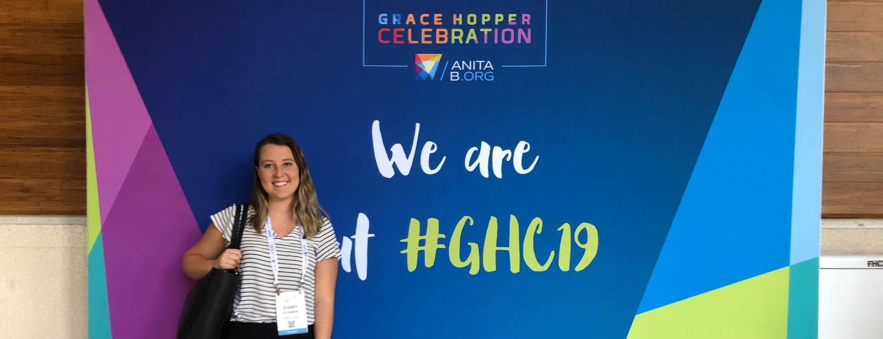 a young woman in business casual wear stands in front of a banner for the Grace Hopper celebration 2019 conference