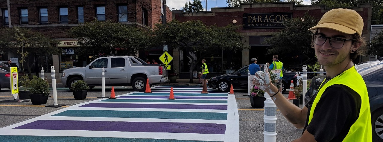 young man in safety vest gestures to a wide crosswalk painted white, purple and green