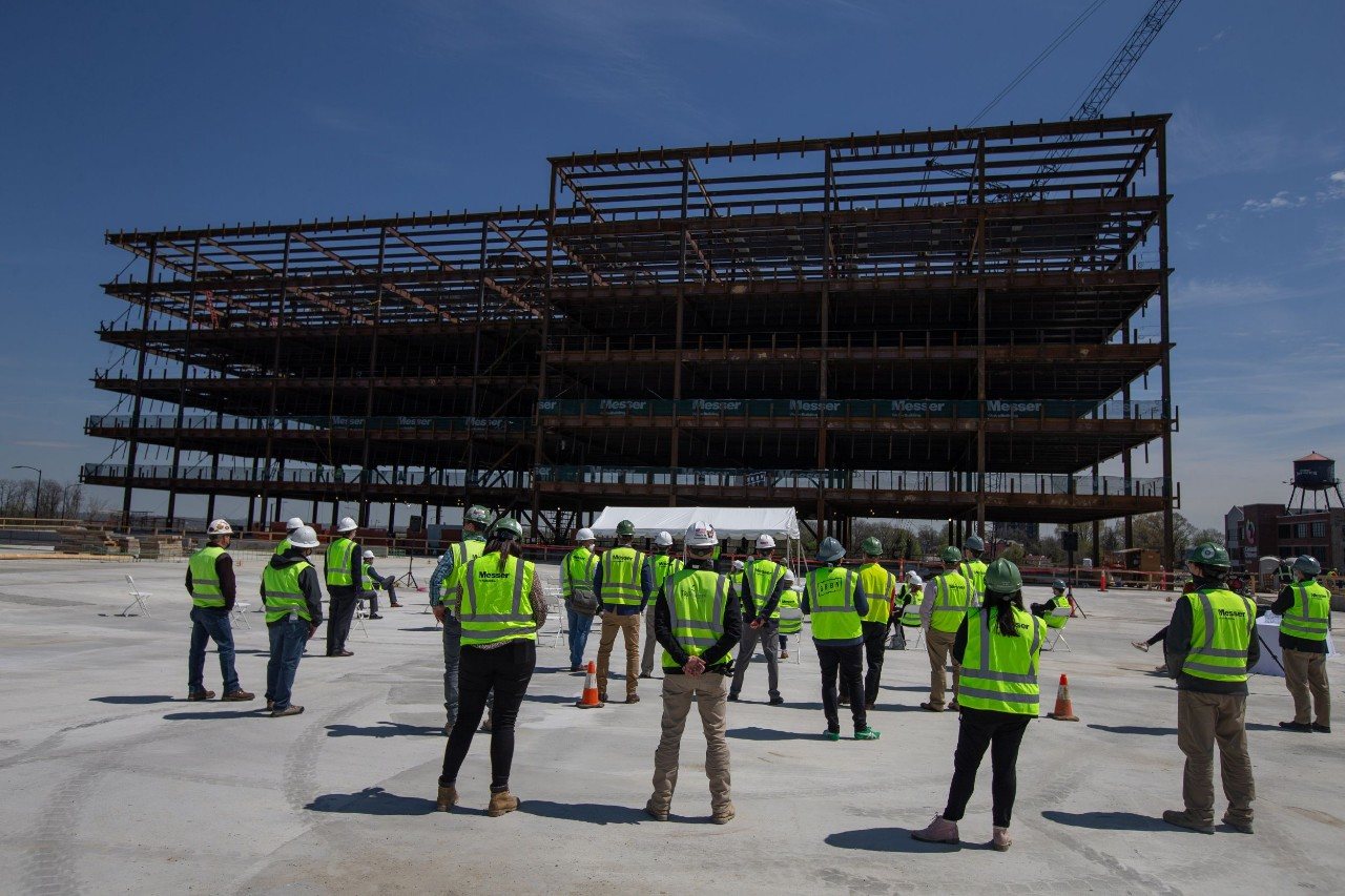 A group of people in safety vests and hardhats stand gathered in front of a steel structure.