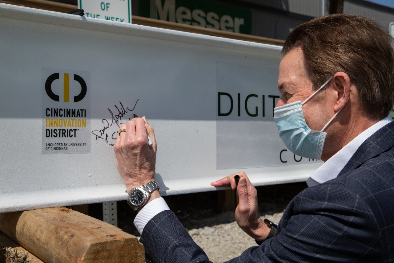 A man in a face mask signs a steel beam that says Digital Futures and Cincinnati Innovation District.