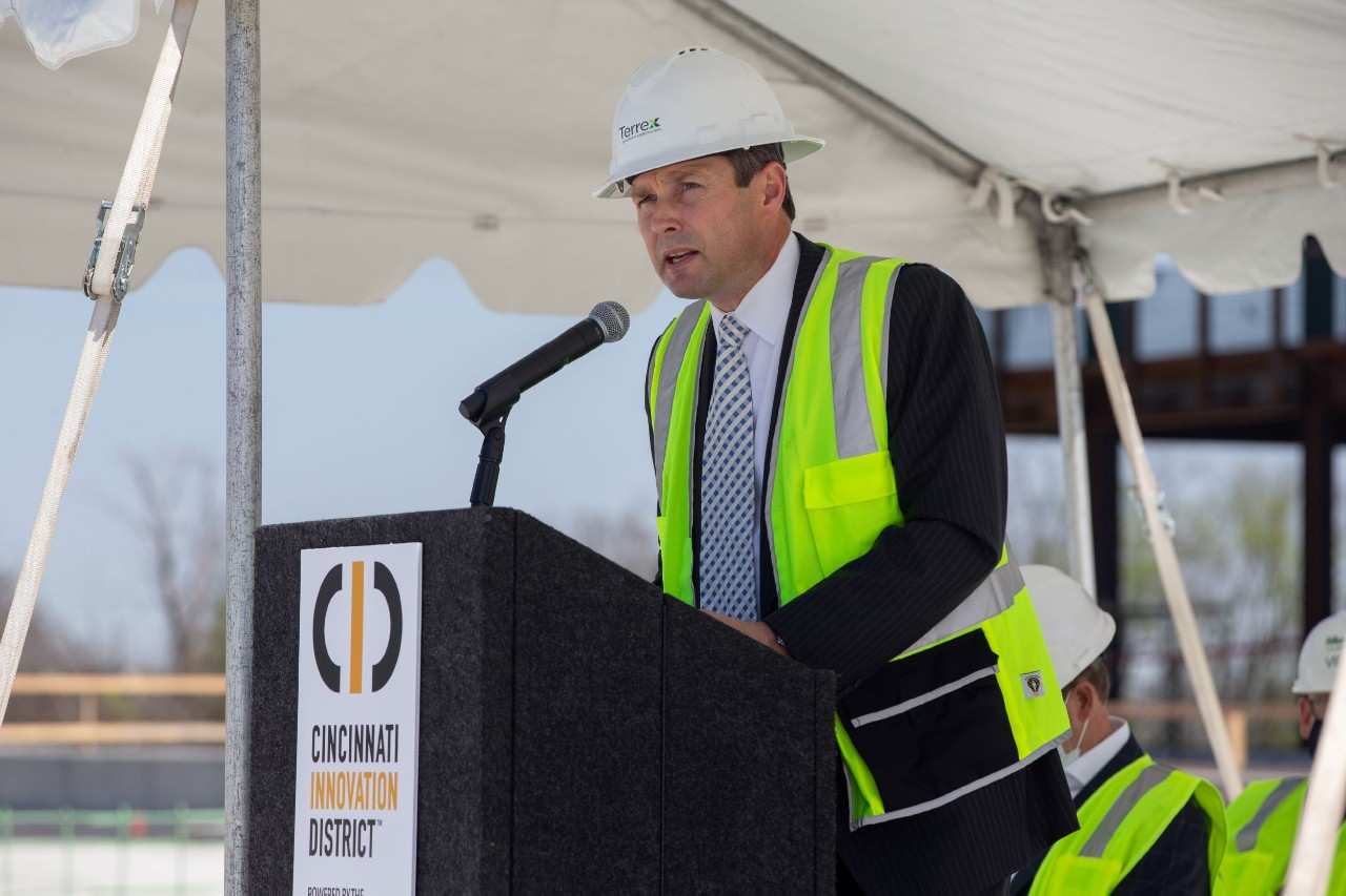 A man in a hardhat and safety vest stands at a podium.