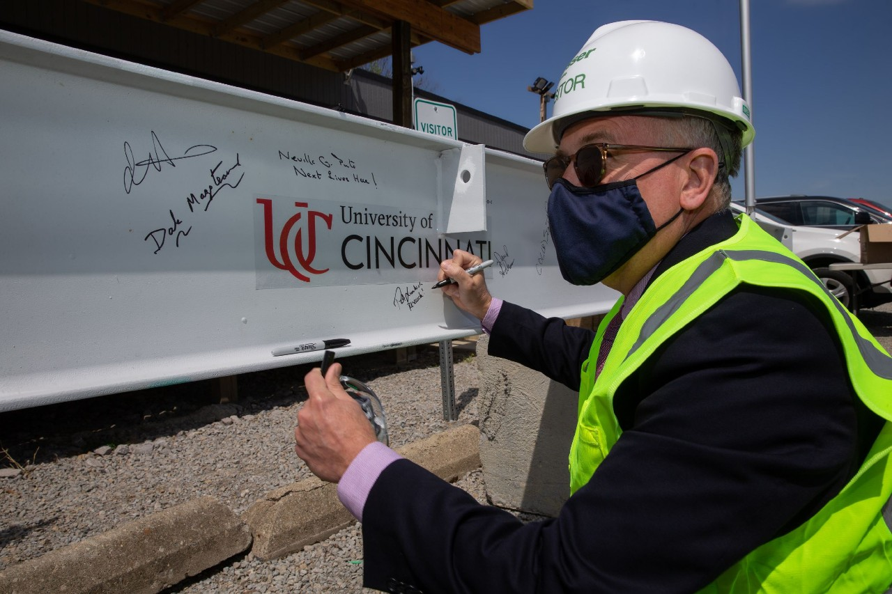 A man in a hardhat and safety vest signs a steel beam that says University of Cincinnati.