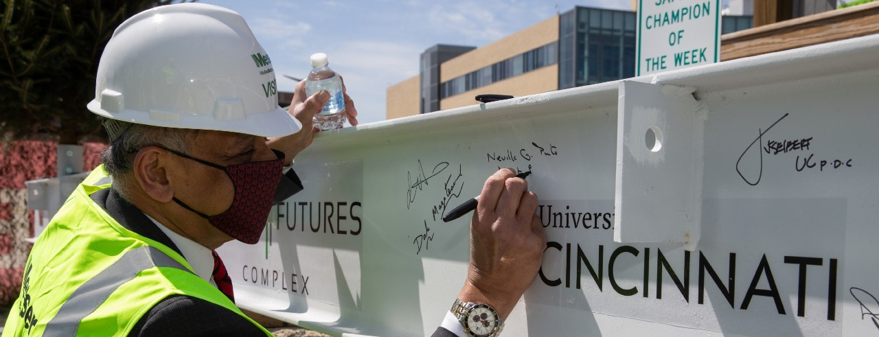 UC President Neville Pinto signs the last steel beam for the new Digital Futures Building.