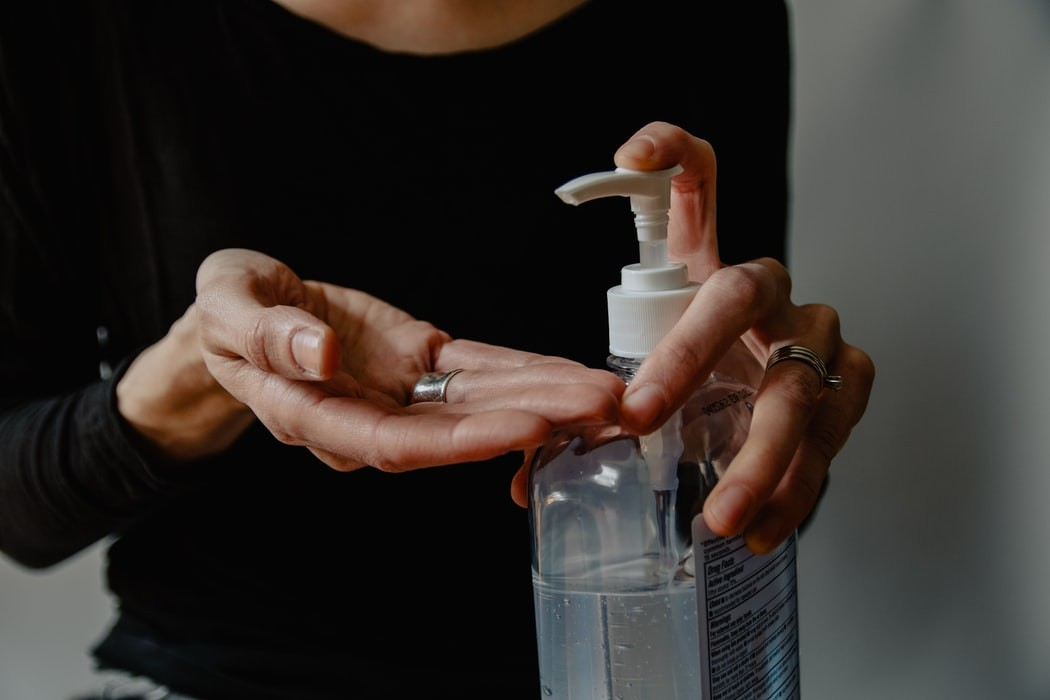 image of a person using hand sanitizer