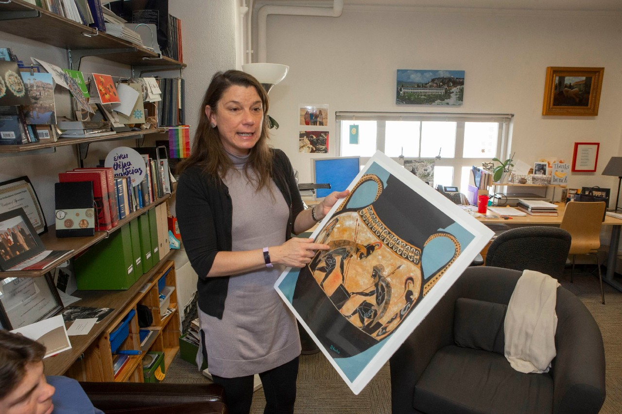 UC Classics professor Kathleen Lynch holds up a painting of an ancient vase in her office.