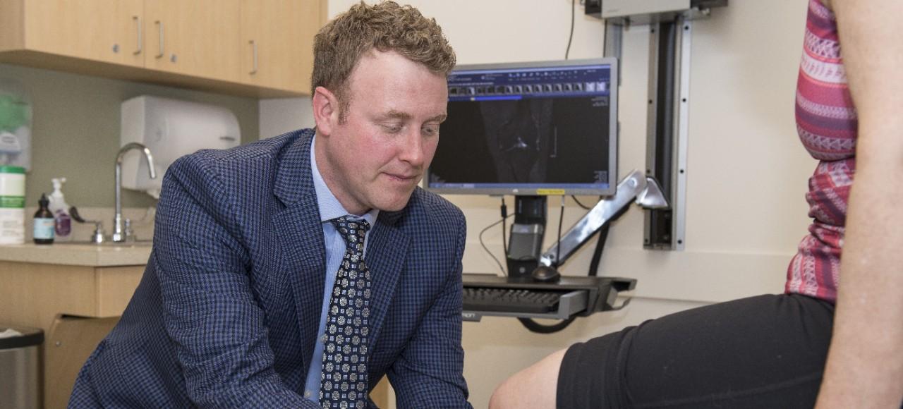 UC Health orthopedic surgeon examines a patient's knee