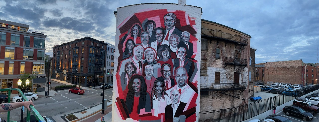 Urban mural with red and black collage of 19 portraits