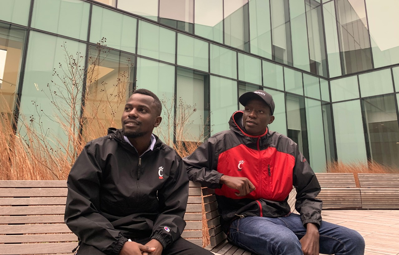 Two students from Tanzania sitting outside wearing UC gear