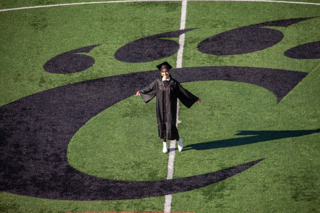 UC grad Sydney O'Connor stands in the Bearcat C-paw on the soccer field.