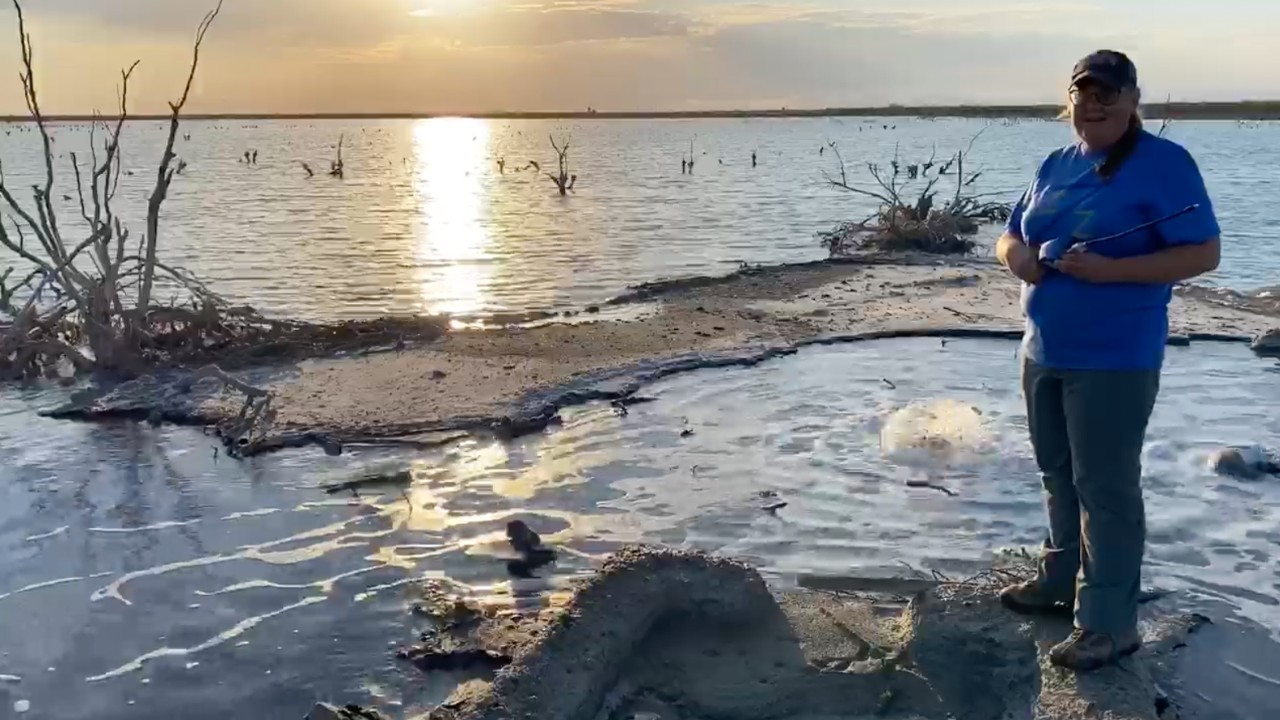 UC associate professor Amy Townsend-Small stands in front of a small lake created by a bubbling oil well and the setting sun behind her.