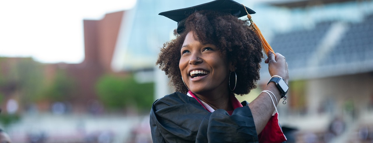 A UC student smiles in her cap and gown as she turns her tassel to mark her commencement.