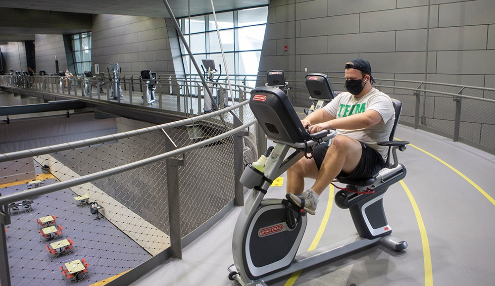a man wearing a face mask exercises on an exercise bike