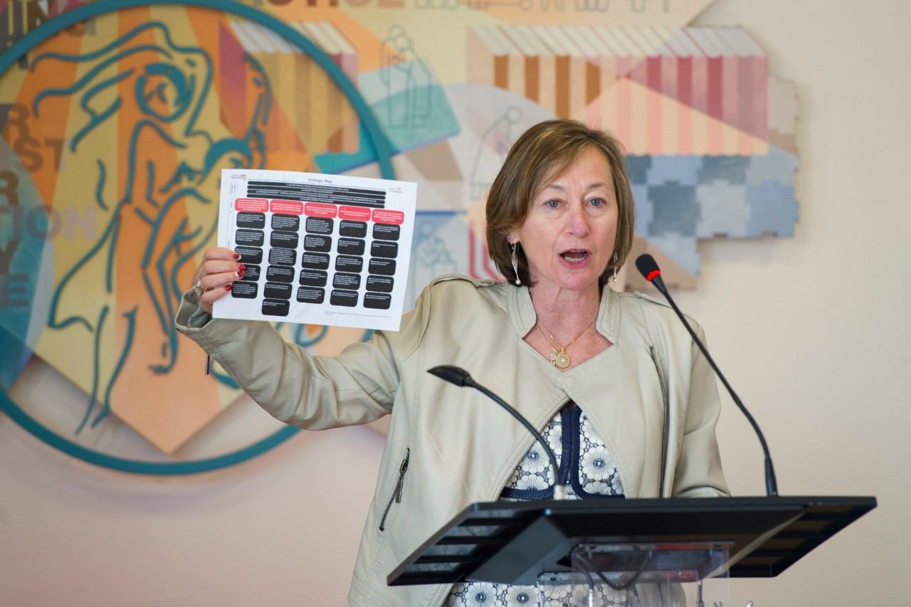 Greer Glazer, dean of the UC College of Nursing, speaking at a podium, holding up a copy of the college's strategic plan