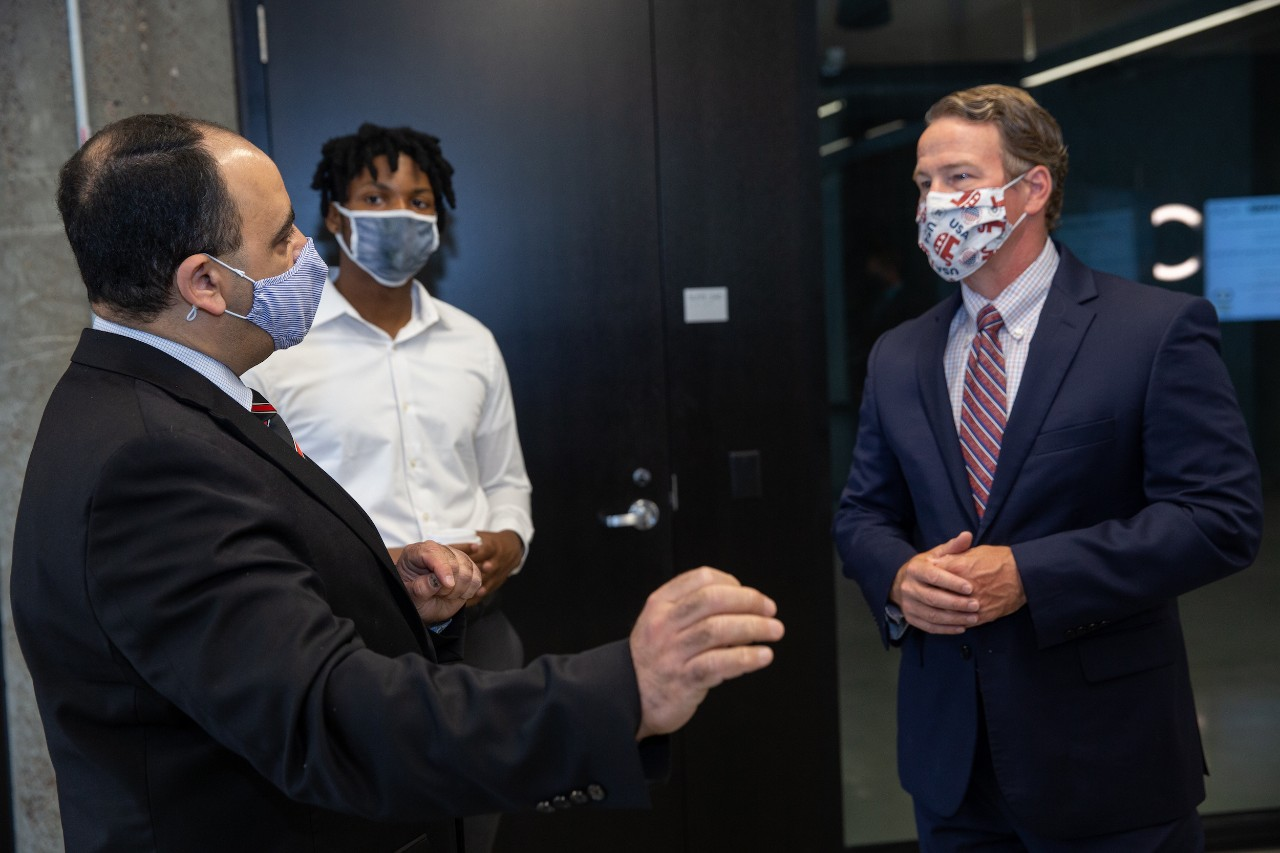 Three men stand together in UC's 1819 Innovation Hub wearing PPE masks.