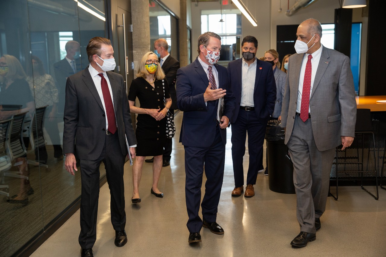 Several UC leaders and 1819 industry partners walk through the 1819 halls with Ohio Lt. Gov. Jon Husted in center.