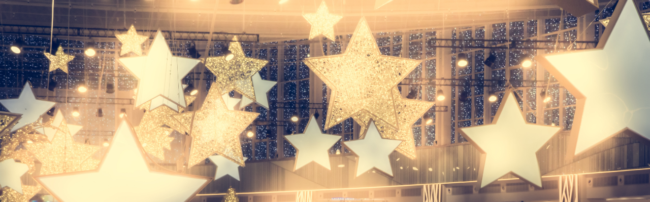 glittery glowing golden star shaped lights hanging from the ceiling of a room with high windows in the background