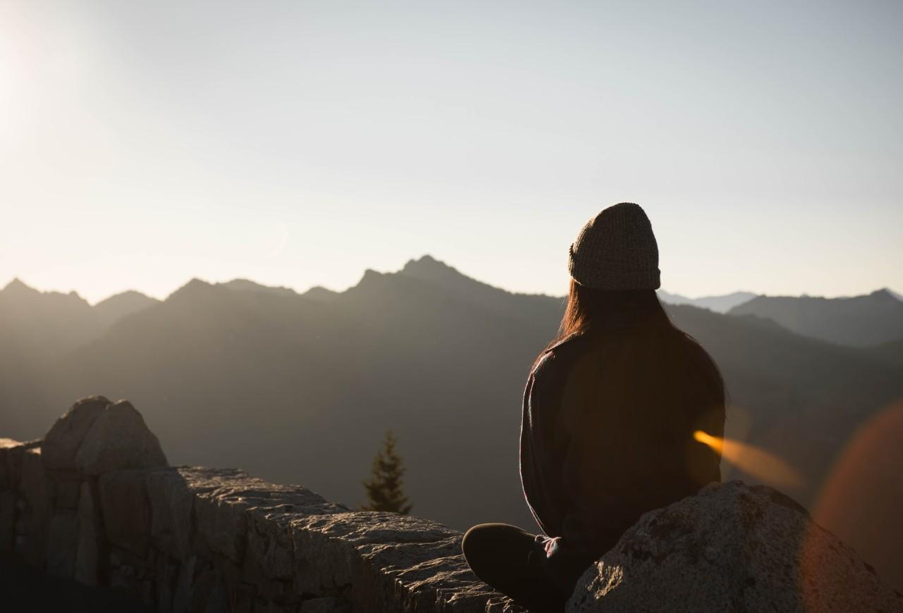 woman sitting watching a beautiful sunlit mountain top
