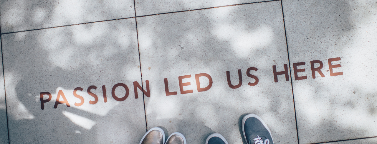 """two sets of feet in sneakers stand on a sidewalk, near lettering that reads """"Passion led us here"""""""