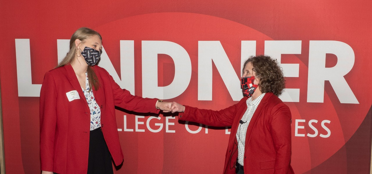 two women in red blazers and white blouses fist bump in front of a red LINDNER banner
