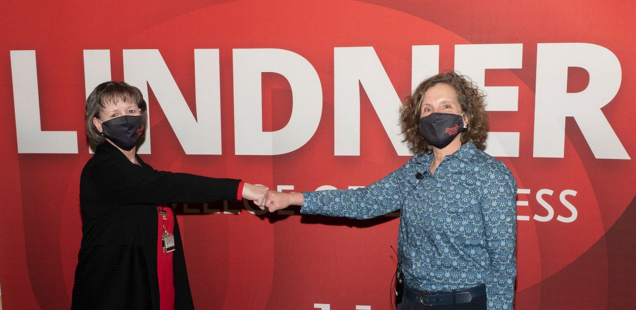 A woman in a black sweater fist bumps with another woman in a blue patterned blouse in front of a red banner with LINDNER in white