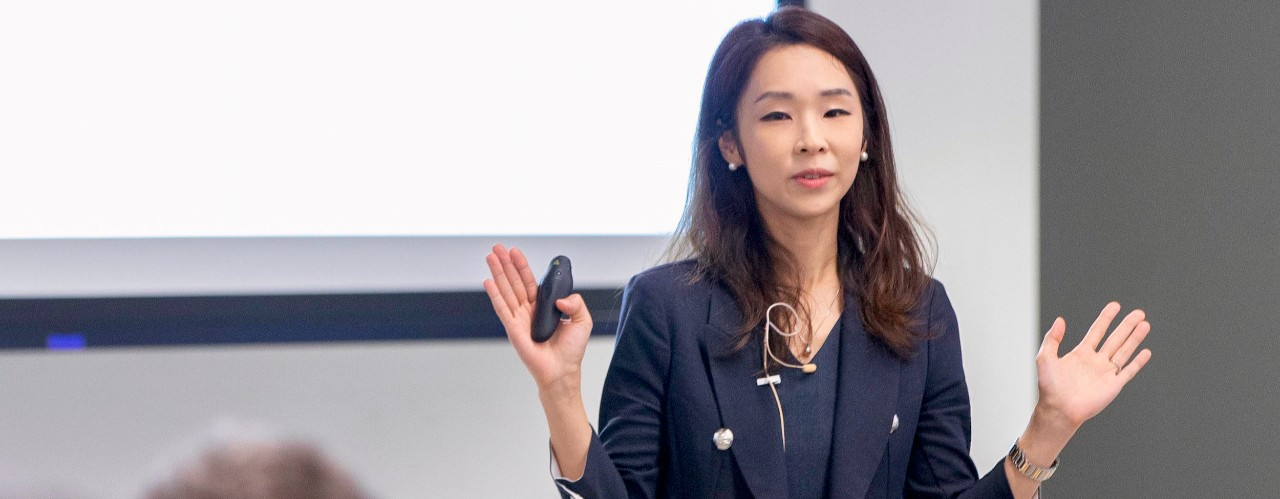 A woman, Yoonjee Park, stands in front of a panel of judges in the 1819 Innovation Hub Venture Lab..