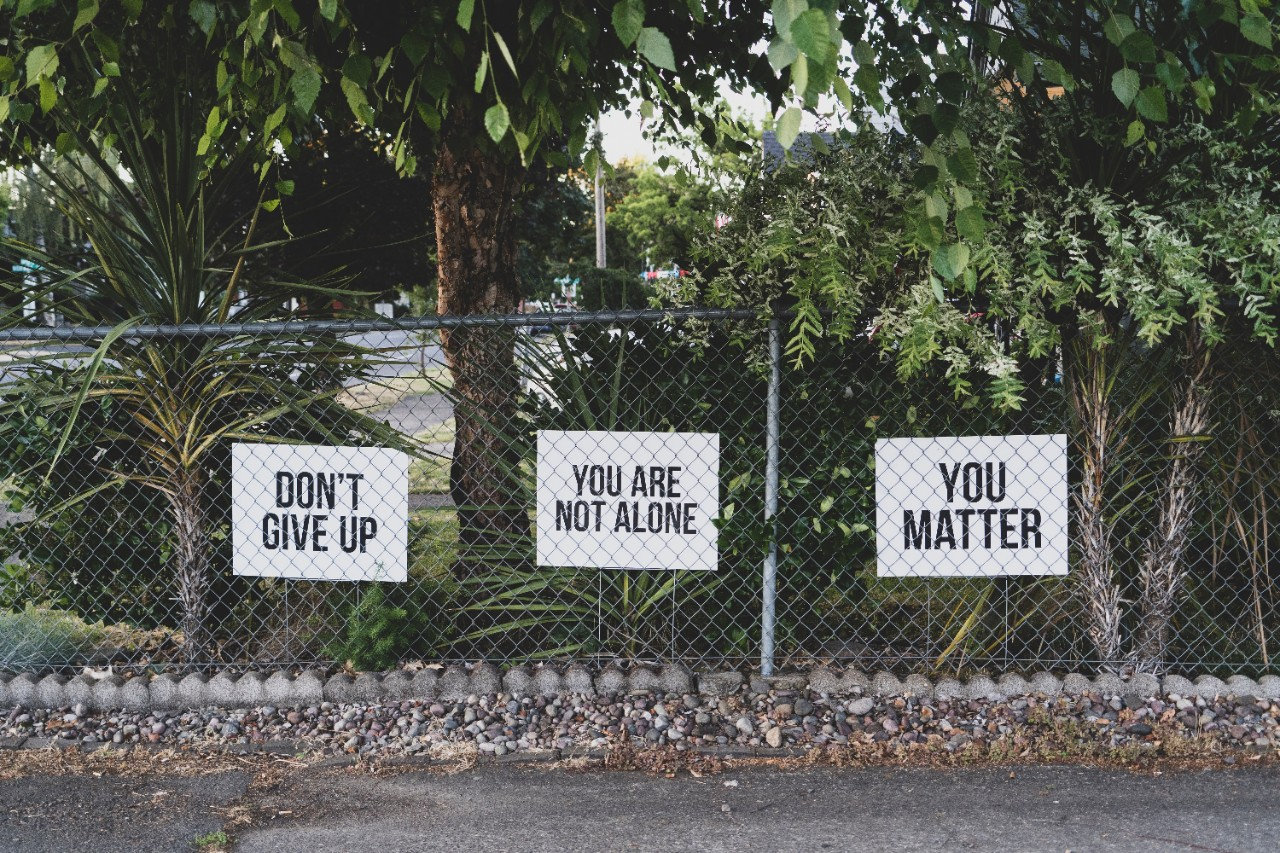 Three signs on a chain-link fence read dont give up, you are not alone and you matter.