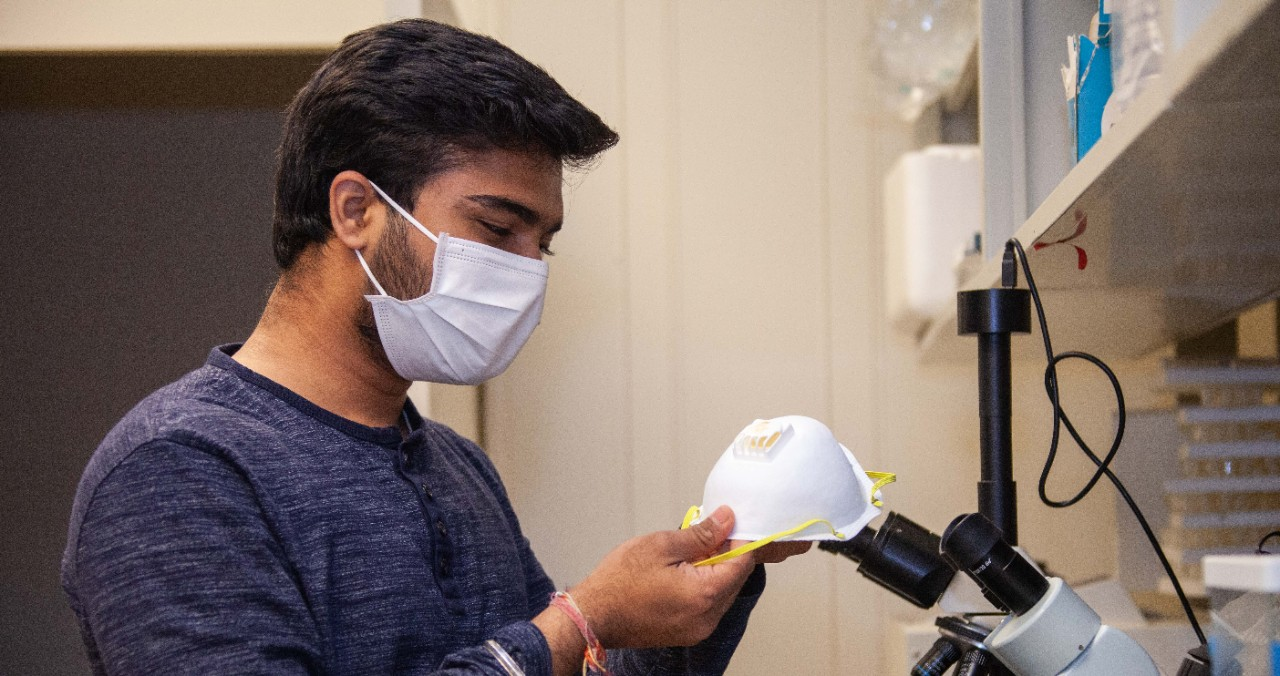A UC student wearing a face mask holds another mask in a UC lab.