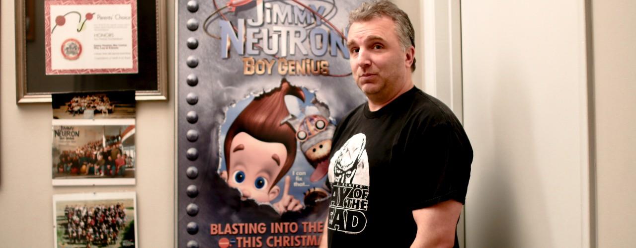 UC assistant professor Mike Gasaway stands in front of his Jimmy Neutron: Boy Genius poster.