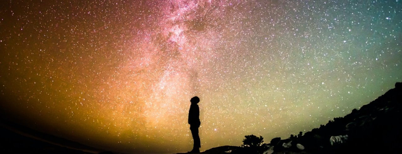 silhouette of person looking at starry night sky