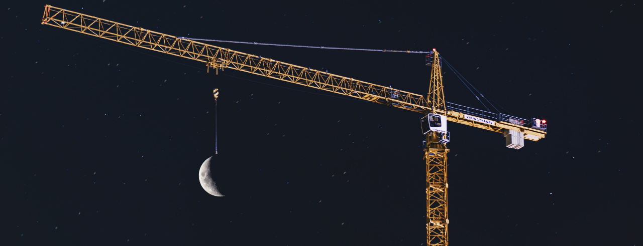 A yellow construction crane against the night sky, the moon appearing to hang from its chain