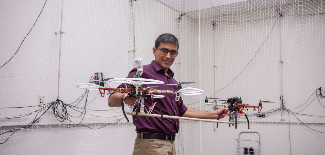 Manish Kumar holds up two drones in his lab.