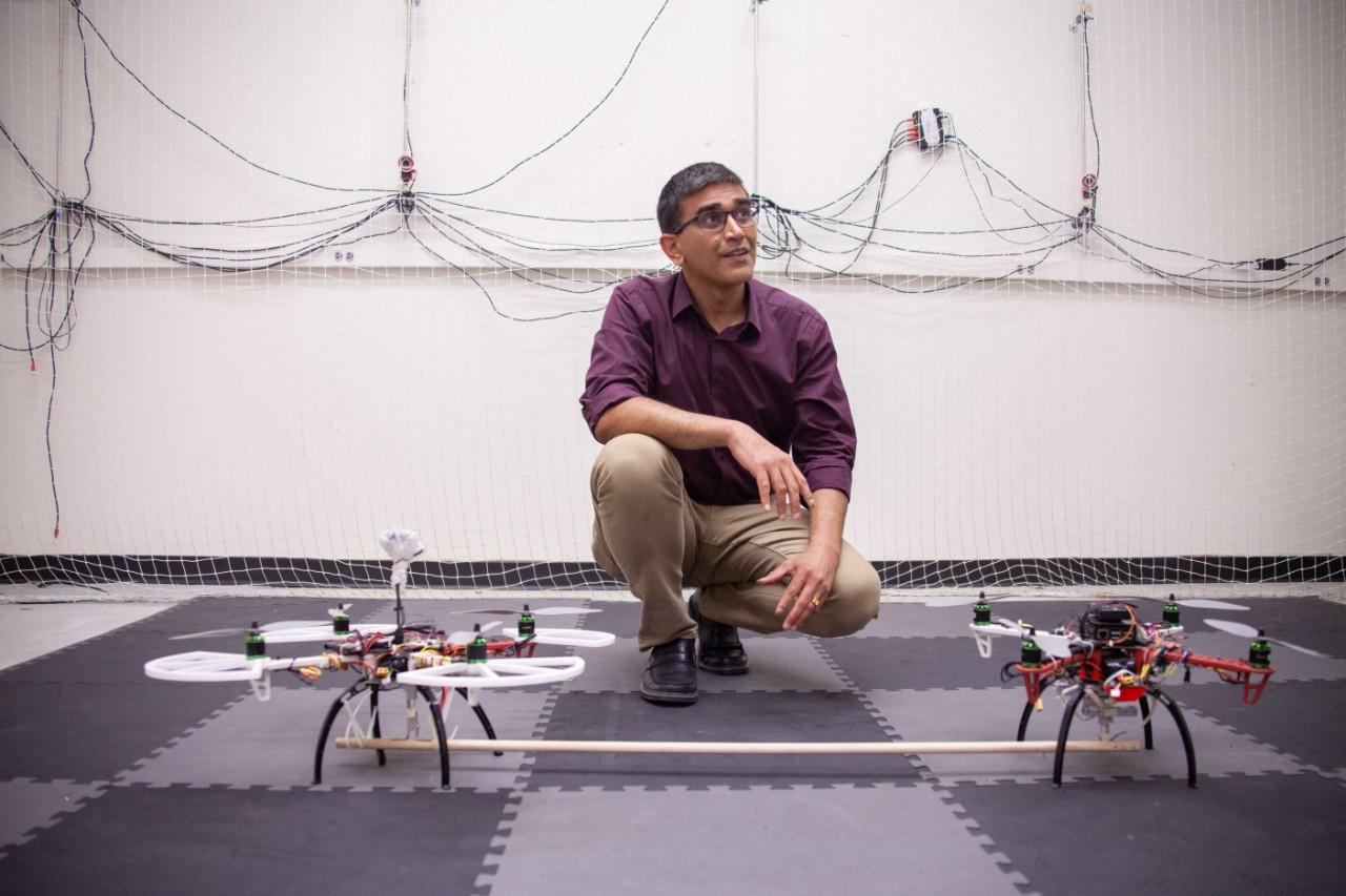 Manish Kumar kneels in front of twin drones in his flight cage.