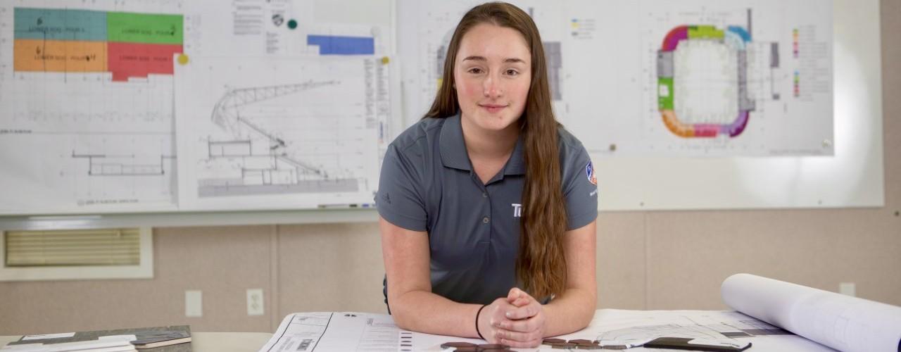 UC women co-op student leans on blueprints spread across a table.