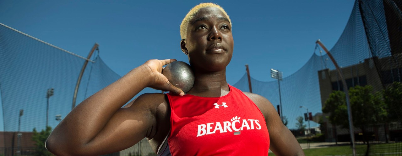 Annette Echikunwoke, UC Olympic hammer throw athlete stands holding a sport discus.